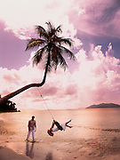A man pushes his wife on a tire swing hanging off a palm tree on a carribean beach