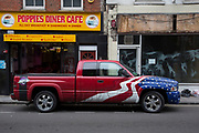 Stars and stripes flag painted pickup truck outside Poppies Diner, and American style cafe in East London, UK.