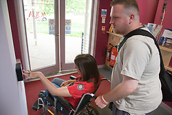 Young woman with cerebral palsy pressing a disability access door button to exit a café,
