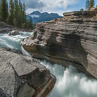 Banff National Park, Alberta Canada. The Mistaya River plunges into Mistaya Canyon, a narrow slot it has eroded over millenia. Behind is Mount Sarbach.