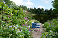 A seating area and table surrounded by herbaceous borders on the lower west terrace at High Glanau Manor Gardens, Lydart, Monmouth, Gwent, UK