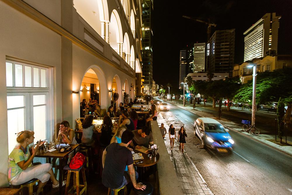 People are seen hanging out at Casa Veranda bar inside Casa Veranda building on Rothschild Boulevard, in Tel Aviv's Lev Hair neighborhood