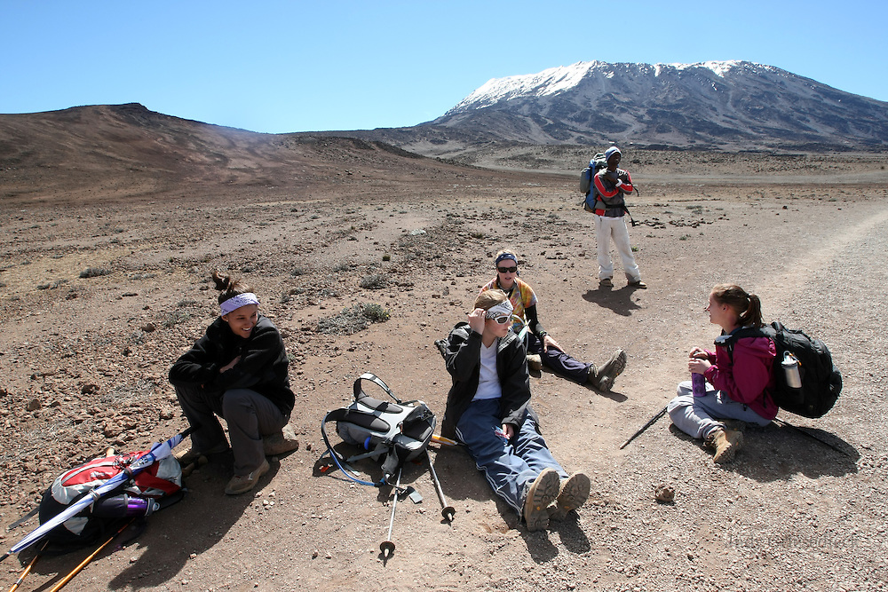 Climbers take a break after the morning climb, beginning to feel the effects of the altitude as they reach The Saddle, the long flat road that seems to go on forever as they approach the last hut before attempting the summit.
