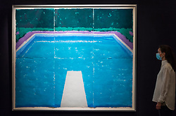 "© Licensed to London News Pictures. 23/07/2020. LONDON, UK. A staff member next to ""Pool on a Cloudy Day with Rain (Paper Pool 22) (1978) by David Hockney, estimate: £4-6 million. Preview of works on display at Sotheby's London ahead of a one-off auction on July 28.  Titled 'Rembrandt to Richter', the sale will offer the very best from Old Masters, Impressionist & Modern Art, Modern & Post-War British Art and Contemporary Art.  The exhibition is open to the public at Sotheby's New Bond Street galleries until July 28. [Image embargoed for release until 9am BST 24 July 2020].  Photo credit: Stephen Chung/LNP"