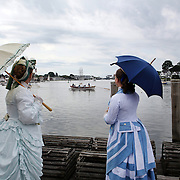Karlee Etter (left) and Amanda Nichols in historic costume watching the  Whaleboat parade during the relaunch of Mystic Seaport Museum's flagship whaling ship Charles W. Morgan. The historic waterfront at Mystic seaport. Mystic, Connecticut. 21st July 2013. Photo Tim Clayton