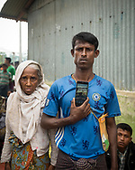 A Rohingya Muslim from Myanmar, newly arrived at Kutupalong refugee camp in Bangladesh, stands with his mother and holds up his phone to show a picture of his cows and home, which they fled earlier this month, walking for 17 days to Bangladesh. (October 29, 2017)