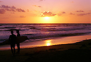 Silhouette of surfers looking out to ocean at Carlsbad State Beach, CA at sunset.<br /> <br /> CONTACT US FOR PRICING AND USAGE RATES