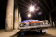 An old car lies unmaintained below a highway overpass in Seattle, Washington.