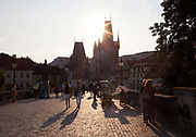 People walk over the Charles Bridge in the warm afternoon light, Prague old town, Czech Republic. .