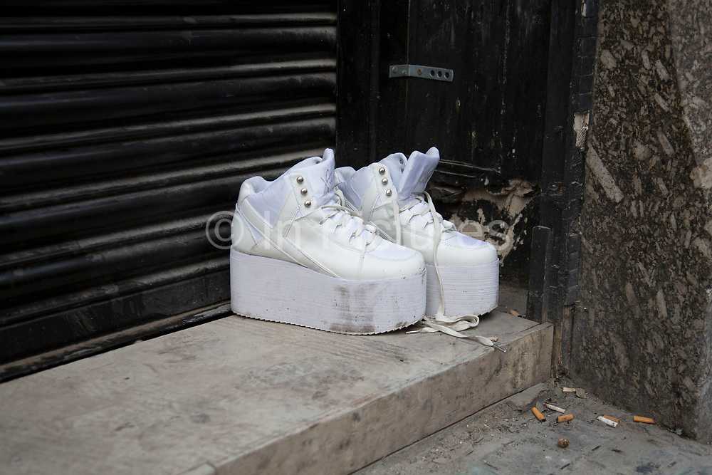 Pair of abandoned platform style trainers, discarded in a doorway strewn with cigarette butts. Tells a story of a night out which went slightly wrong. London, UK.