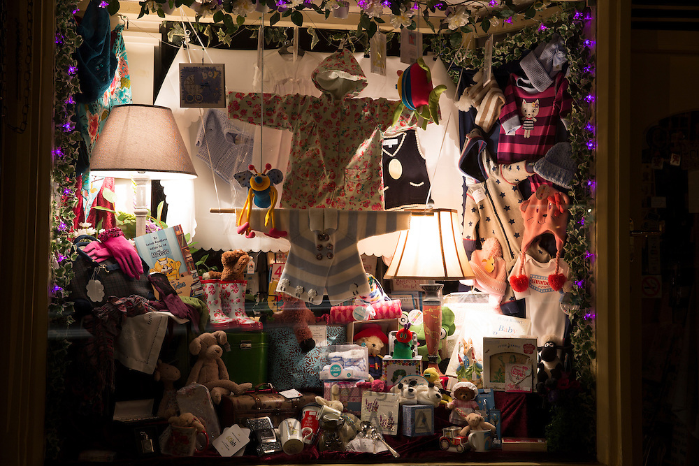 Window display at gift and souvenir shop selling toys, linens, lamps etc. along Burford High Street at night, The Cotswolds