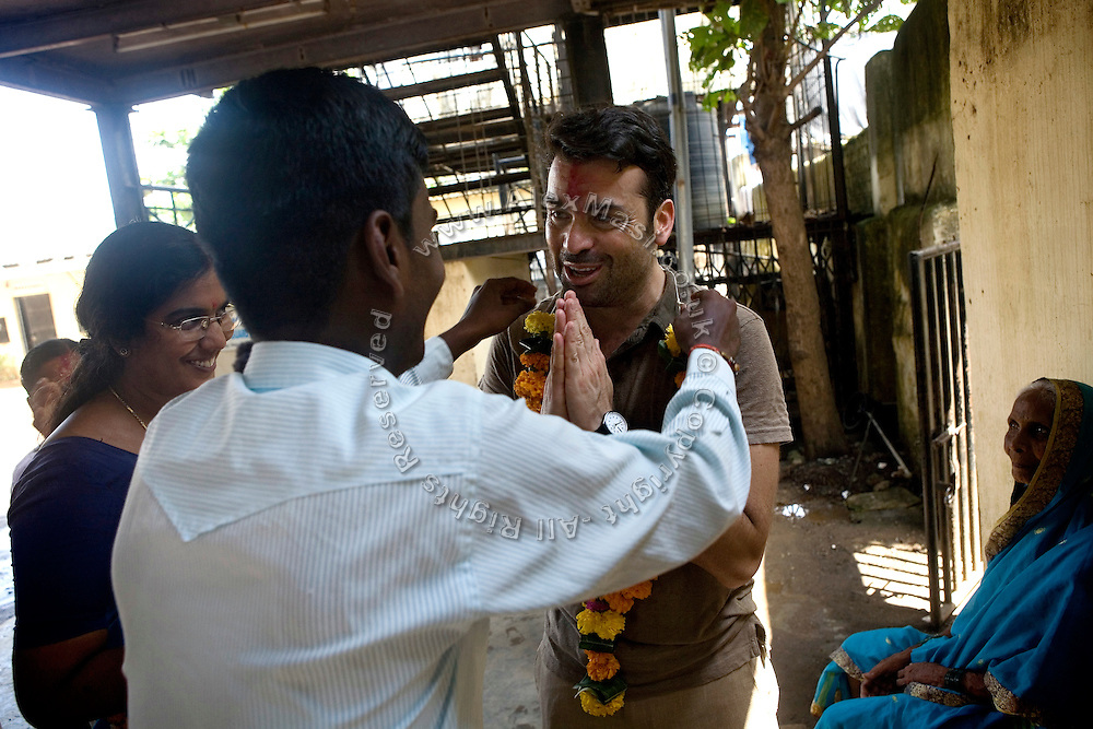 Jaume Sanllorente, the director general of Sonrisas de Bombay is receiving a blessing and a garland by a community member during the celebrations for the Hindu festival of Durga Puja in the courtyard of a school run by the fast-growing Spanish NGO in Mumbai, India.