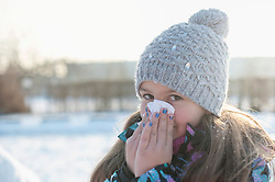 Portrait of girl sneezing in winter