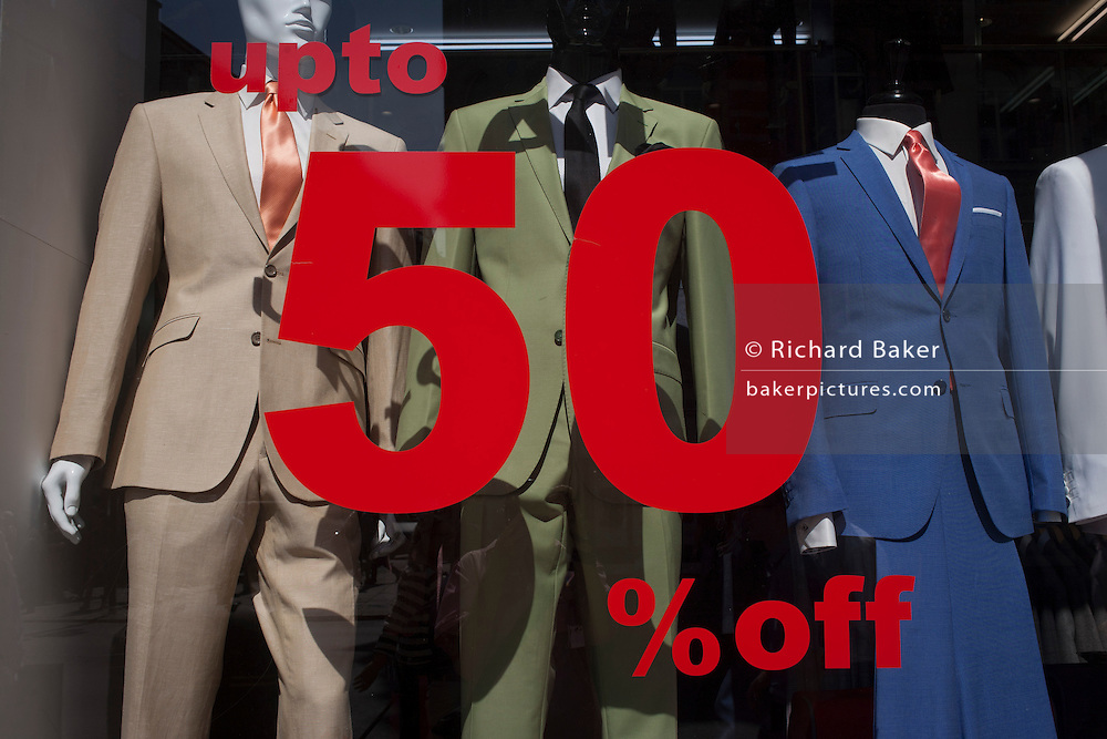 Menswear suits discounted by 50% in the window of an Oxford Street shop window in London, UK.