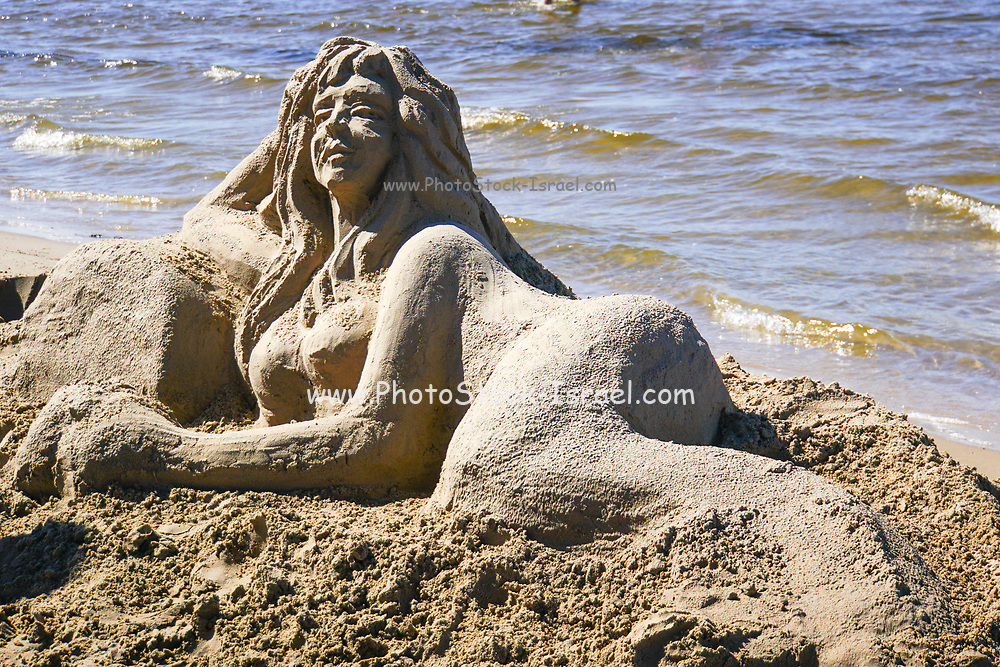 Artist makes a sand sculpture of a Mermaid. Photographed in Jurmala, Latvia