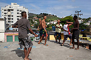 Young men guys on a rooftop with buildings in the background in Vila Valquiere, West Zone Zona Oueste, Rio de Janeiro
