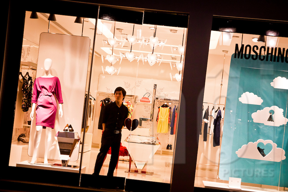 Window of Moschino shop in Hanoi, Vietnam, Asia. A seller looks the photographer through the window