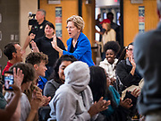 """21 OCTOBER 2019 - DES MOINES, IOWA: US Senator ELIZABETH WARREN (D-MA) """"high fives"""" a teacher an assembly for students at Roosevelt High School in Des Moines. Sen. Warren talked to students about her journey from childhood in Oklohoma to running for the US Presidency. Sen. Warren is campaigning to be the Democratic nominee for the US presidency in Iowa this week. Iowa traditionally hosts the the first selection event of the presidential election cycle. The Iowa Caucuses will be on Feb. 3, 2020.                 PHOTO BY JACK KURTZ"""