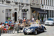 Classic Morgan drop head sports car being driven past diners al fresco at restaurant in Kerk Straat, Damme, Belgium