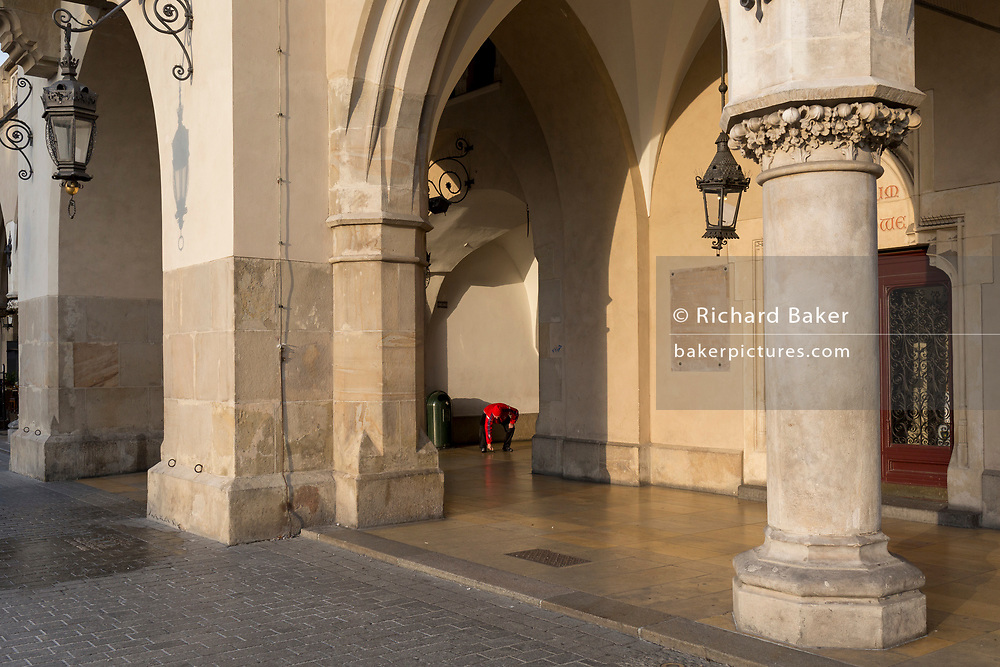 A local authority street cleaner scrapes gum from pavements and passageways of the Cloth Hall on Rynek Glowny market square, on 23rd September 2019, in Krakow, Malopolska, Poland.