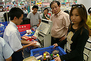 (MODEL RELEASED: EXCEPT FOR CHECKOUT BOY) Finishing their weekly grocery shopping expedition to Ito Yokado, a Japanese supermarket chain, the Dongs of Beijing, China, go through the checkout line. In many restaurants and markets in China, much of the seafood is sold live as a guarantee of freshness. In other ways, the supermarket hews closely to Western models, right down to the workers offering samples. (Supporting image from the project Hungry Planet: What the World Eats). The Dong family of Beijing, China, is one of the thirty families featured, with a weeks' worth of food, in the book Hungry Planet: What the World Eats.