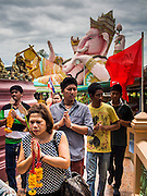 31 AUGUST 2014 - SARIKA, NAKHON NAYOK, THAILAND: People walk through Shri Utthayan Ganesha Temple in prayer during the Ganesh Festival. Ganesh Chaturthi, also known as Vinayaka Chaturthi, is a Hindu festival dedicated to Lord Ganesh. It is a 10-day festival marking the birthday of Ganesh, who is widely worshiped for his auspicious beginnings. Ganesh is the patron of arts and sciences, the deity of intellect and wisdom -- identified by his elephant head. The holiday is celebrated for 10 days, in 2014, most Hindu temples will submerge their Ganesh shrines and deities on September 7. Wat Utthaya Ganesh in Nakhon Nayok province, is a Buddhist temple that venerates Ganesh, who is popular with Thai Buddhists. The temple draws both Buddhists and Hindus and celebrates the Ganesh holiday a week ahead of most other places.    PHOTO BY JACK KURTZ