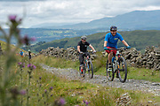 Two men mountain biking along a cycle path on the 13th June 2019 near Kentmere in the Lake District in the United Kingdom.