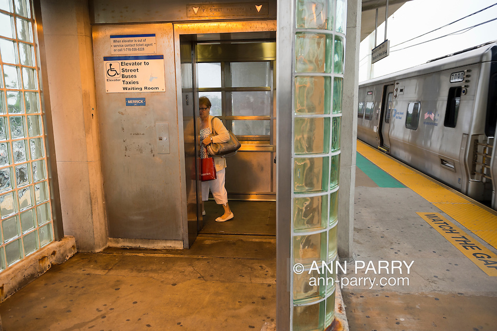 During evening rush hour, woman passenger gets on elevator on elevated platform of Merrick train station of Babylon branch, after MTA Metropolitan Transit Authority and Long Island Rail Road union talks deadlock, with potential LIRR strike looming just days ahead.