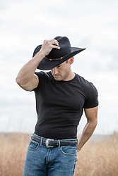 muscular cowboy in a black tee shirt outdoors