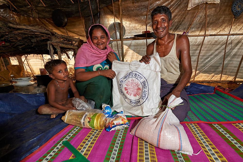 In their family's makeshift shelter in the Mainerghona Refugee Camp near Cox's Bazar, Bangladesh, Kamal Hasom and his wife Dildar Mamaz pose with food supplies they received from Caritas on October 27, 2017. Their 4-year old daughter Nuralam watches. <br /> <br /> They are among the more than 600,000 Rohingya who since August have fled violence in Myanmar for safety in Bangladesh.<br /> <br /> Hasom said they fled their village in Myanmar in late September after their house was burned by the Myanmar military.
