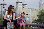 A woman sits in the shade with a young girl during a daytrip to the Tower of London.