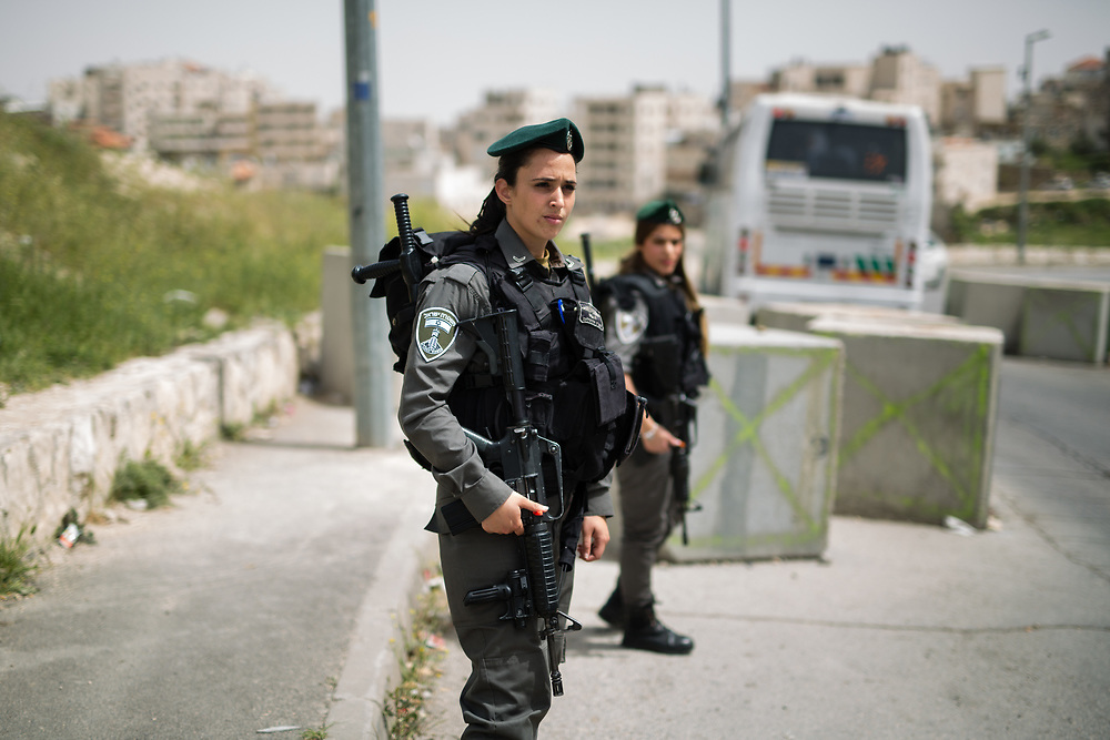 Israeli Border Police Women Corporal Mor Hadad (L) and  Staff Sergeant Chen Cohen (R) stand guard at the exit of the East Jerusalem neighborhood of Issawiya, in Jerusalem, Israel, on April 10, 2016.