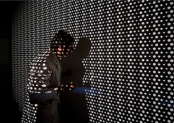 SOLMS, GERMANY - MAY-18-2009 - In one of the final stages of quality control, a technician projects a uniform pattern through a Leica lens, on to the wall, which allows for visual inspection of edge to edge image sharpness. (Photo © Jock Fistick)