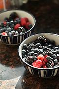 Two bowls of summer berries -- including raspberries, blackberries and blueberries -- on a granite countertop.