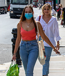 © Licensed to London News Pictures. 23/07/2020. London, UK. A shopper in Chelsea wears a mask while shopping on the Kings Road before it becomes compulsory in shops in England tomorrow. Face masks will be compulsory in shops, takeaway cafes and supermarkets from 24th July and enforced by the Police, with anyone who fails to wear one liable to a £100 fine. Photo credit: Alex Lentati/LNP