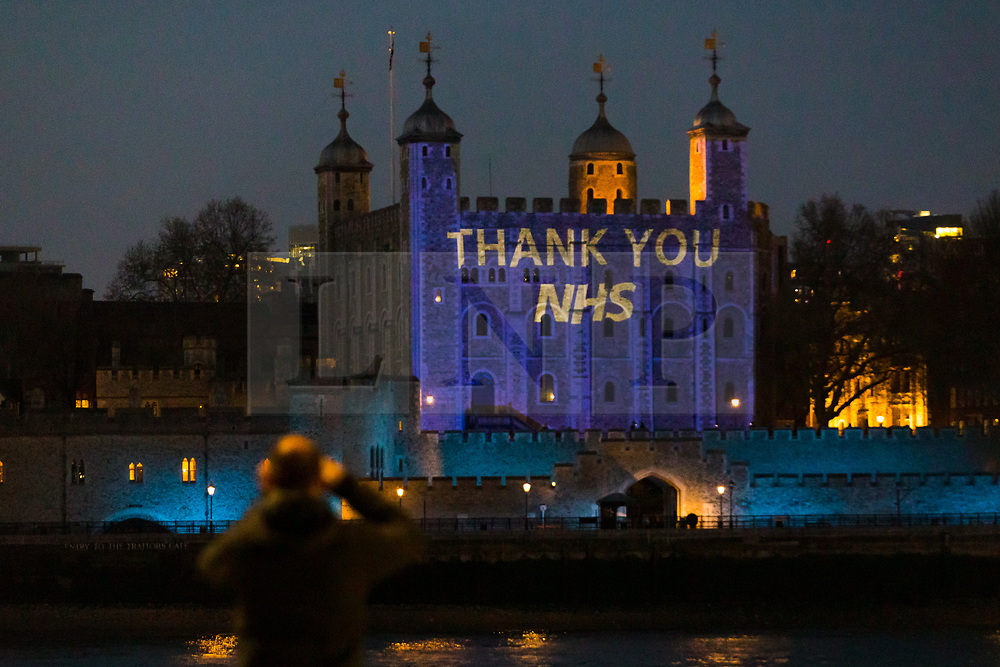 © Licensed to London News Pictures. 09/04/2020. London, UK. A man stops briefly take a photograph of light projections onto the Tower of London this evening in recognition and appreciation of National Health Service (NHS) and key workers during the ongoing COVID-19 coronavirus epidemic. Photo credit: Vickie Flores/LNP