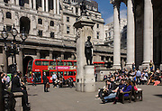 Lunchtime spring crowds enjoy warm weather beneath the war memorial at Cornhill in the City of London.