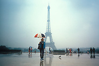 Woman with French flag umbrella at the Eiffel Tower