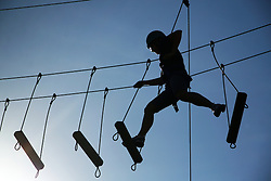 Walking 30 feet above ground on only suspended planks of wood, Anne Dahlman makes a leap of faith as her next step swings underneath her feet.