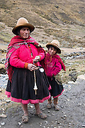 A woman, spinning alpaca wool, poses with her daughter  on the trail to Q'eros in the Cordillera de Paucartambo, Andes Mountains, Peru on September 15, 2005. The Q'eros, a Quecha people living in the Peruvian Andes, are considered the last direct descendants of the Incas and proudly maintain many of the ancient traditions.