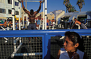 Athletic young men do pull-ups and weight exercises on gym equipment at the outdoor gym on Muscle Beach, on 18th May 1996, on Venice Beach, Los Angeles, California, USA.