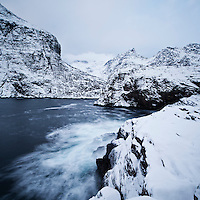 Snow covered cliffs and mountains rise from sea, Å I Lofoten, Lofoten Islands, Norway
