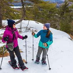 Two women snowshoeing near the summit at Loon Echo Land Trust's Bald Pate Mountain Preserve in South Bridgton, Maine.