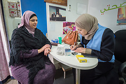 26 February 2020, Abu Dis, Palestine: 43-year-old Intisar Alafandi (left) from Abu Dis receives nutritional guidance from Dietitian Samah Khatib (right) as she visits the Mobile Diabetes Clinic of the Augusta Victoria Hospital for testing. In an effort to make Diabetes services more accessible to people in the West Bank, the Augusta Victoria Hospital offers a Mobile Diabetes Clinic, which moves around to various locations in the West Bank, offering screening and routine testing for Diabietes and the symptoms it causes.