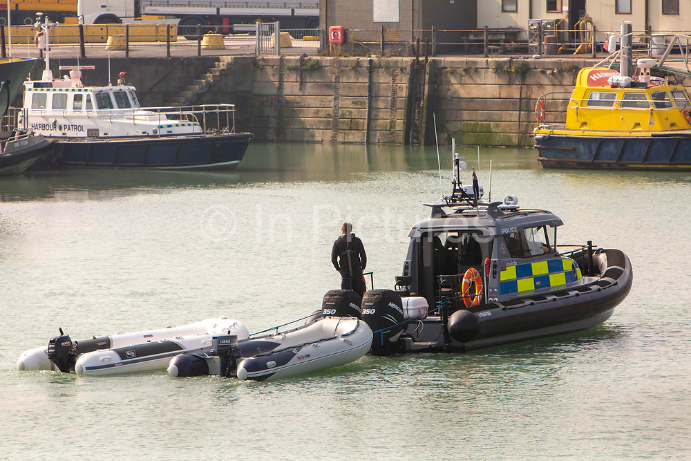 Police officers on a police boat tow two small inflatable dinghies into Dover after migrants were rescued by the RNLI. Migrants arrived into Dover docks on board an RNLI rescue boat after being rescued in the English Channel while crossing in small inflatable dinghies on the 22nd of September 2020 in Dover, Kent, United Kingdom. About 30 men, women and children (including a baby) arrived today on two small boats they were taken off the RNLI boat by UK Boarder Force and put onto a double decker bus.