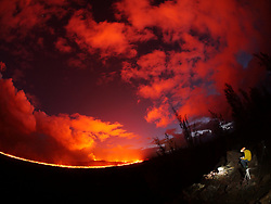 July 4, 2018 - Hawaii, U.S. - Fisheye lens photograph of a USGS geologist making observations of the fissure 8 lava channel at sunset July 3, 2018. The field crew is at a high point overlooking the channel near where it makes a 90 degree turn around Kapoho Crater and flows south. The glow of the fissure 8 vent is the bright spot in the center of a different cone, Halekamahina. (Credit Image: © USGS/ZUMA Wire/ZUMAPRESS.com)