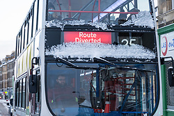 Edinburgh, Scotland, UK. 10 Feb 2021. Big freeze continues in the UK with heavy overnight and morning snow bringing traffic to a standstill on many roads in the city centre. Pic; Lothian bus covered in snow slowly makes way up Leith Walk with diversions in place because of snow . Iain Masterton/Alamy Live news