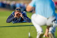 Bernd Wiesberger's caddy checks the line of a pputt on the 18th green during the final round of the Aberdeen Standard Investments Scottish Open at The Renaissance Club, North Berwick, Scotland on 14 July 2019.