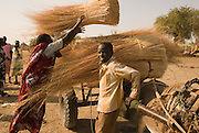 A woman loads hay onto a donkey, at the grass market in Abyei.