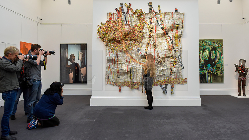 """© Licensed to London News Pictures. 12/05/2017. London, UK.   Members of the media photograph a staff member viewing """"Earth Developing More Roots"""", 2011, by El Anatsui (Ghana) (Est. GBP 650-850k) at the preview for the first sale dedicated to Modern and Contemporary African Art at Sotheby's New Bond Street.  The sale features over 115 artworks by over 60 different artists from 14 countries across the continent. Photo credit : Stephen Chung/LNP"""